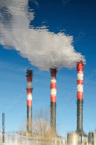 Staande foto Industrial geb. The smoking chimneys of the plant are reflected in the water. Plant pipes with smoke against clear blue sky. Abstract background with distortion of reflection on the water surface