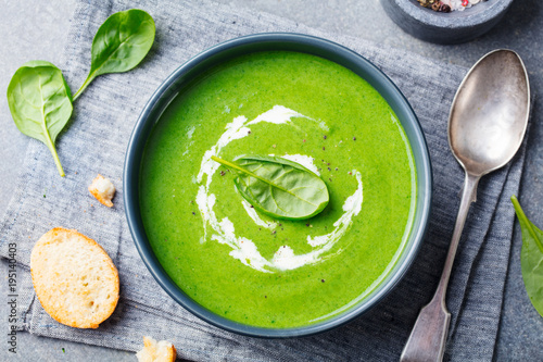 Spinach soup with cream in a bowl. Top view.