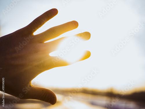 Photo  hand raised against sun yellow silhouette