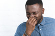 Young african american man touching nose