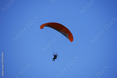 Tuinposter Luchtsport Paraglider flies in blue skies. The glider is a light aircraft plans in the air.