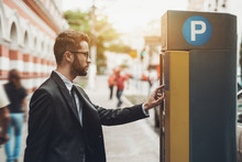 Young Handsome Businessman In Glasses And The Black Business Suit Is Paying His Parking Time Using The Automatic Kiosk; The Confident Male Employee Is Making Payment With Parking Pay Station Terminal