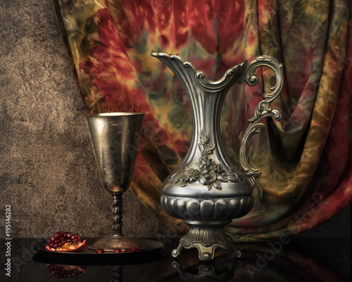 Fotomural  Retro still life with jug wine, metal goblet and a pomegranate
