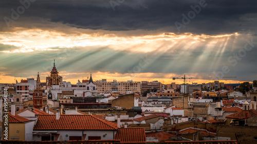 badajoz skyline with sun lights colandose among black clouds
