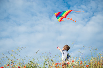 Panel Szklany Niebo little caucasian boy holds string of kite flying in blue sky with clouds in summer with copyspace