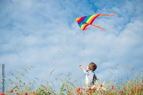Photo little caucasian boy holds string of kite flying in blue sky with clouds in summ