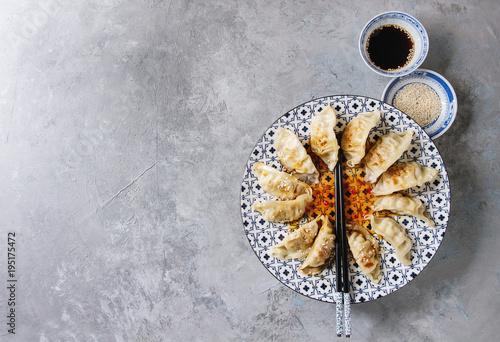 Asian dumplings Gyozas potstickers on white blue ceramic plate served with chopsticks and bowl of soy sesame sauce over grey texture background. Top view, copy space.
