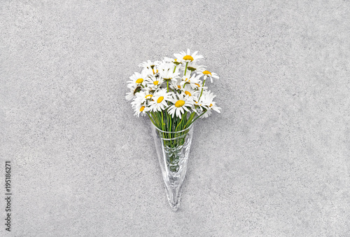 Tuinposter Bloemen Daisies in glass cone on concrete background.