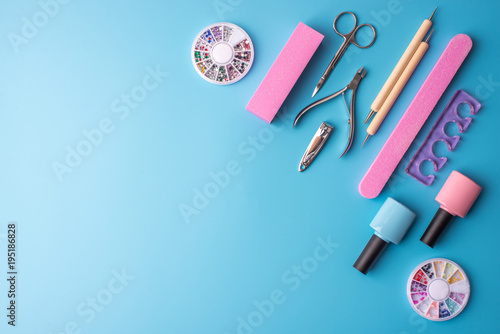 Foto op Aluminium Pedicure A set of cosmetic tools for manicure and pedicure on a blue background. Gel polishes, nail files and clippers, top view