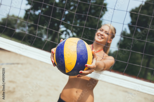 Happy young woman playing beach volleyball on beautiful sunny day.