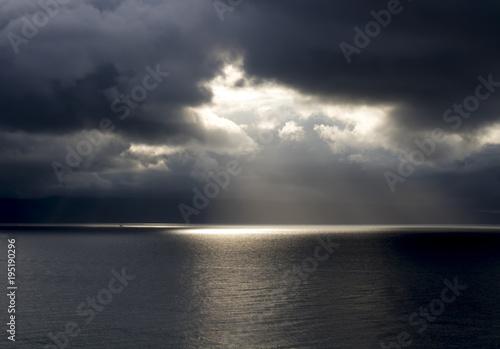 Fotografie, Obraz  Sun Breaks Through Dark Clouds Over Ocean