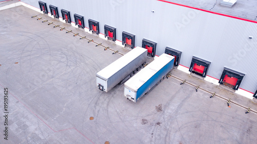 Aerial Shot of Industrial Warehouse Loading Dock where Many Truck with Semi Trailers Load Merchandise. Aerial