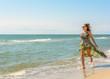 A pretty woman running along a black sea beach in a dress up against the sky