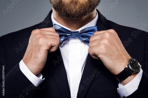 Fotografia Man is fiting up a beautiful bow tie