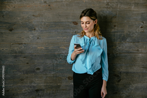 Photo Cheerful attractive woman standing with mobile phone on grey wood background, typing a message