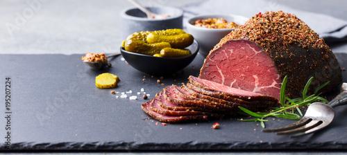 Fotografie, Obraz  Roasted beef, pastrami on slate cutting board. Copy space