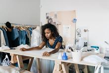 Young Female Fashion Business Entrepreneur Making Custom Hand Made Dress In Studio Workshop