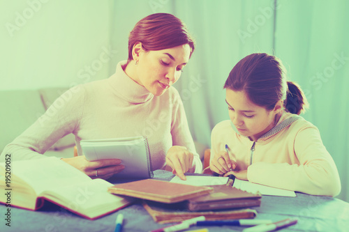 Mother and daughter doing school homework - Buy this stock