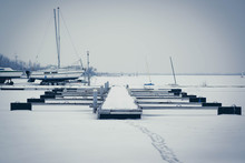 Sailboats Moored In Foggy Harbor. Cold Winter Landscape With Snow And Ice