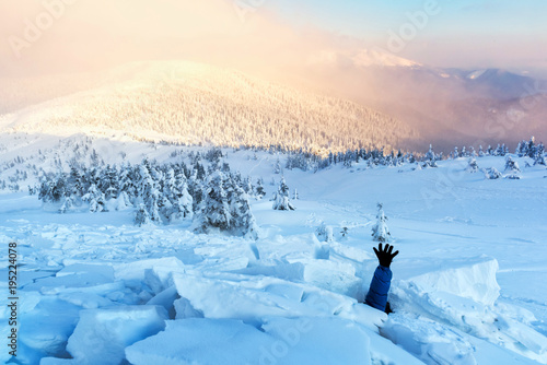 Fotografiet A man covered with a snow avalanche stretches out his hand to help