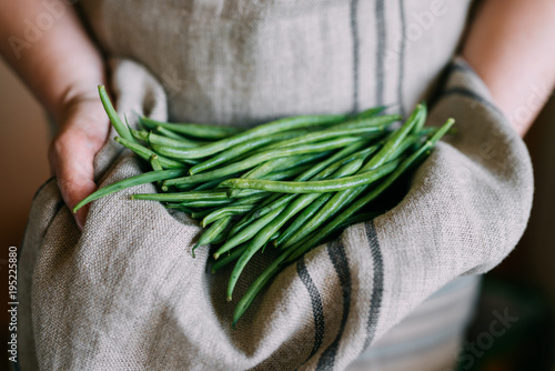 Woman holding green beans in her apron