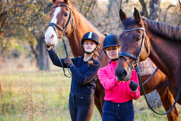 Two teenage girls with their horses in autumn park. Equestrian sport background with copy space