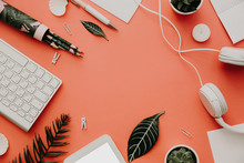 Flat Lay Set Of Office Supplies, Headphones And Keyboard Over Pastel Background. Top View On Various Stationery On Desk. Creative Workspace Background