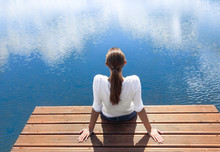 Young Woman Relaxing On A Dock Lake Side. Peace And Serenity Concept.