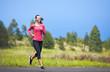 Female runner running on mountain road.