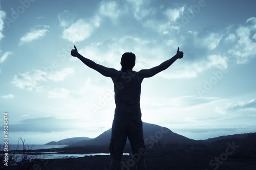 Positive feelings. Man standing on a mountain feeling happy, and free. Thumbs up!