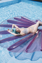 Young Beautiful Woman And A Mermaid Shell Float By The Pool