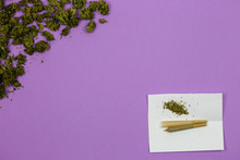 Cone Shaped Rolling Paper With Loose Medical Marijuana Buds And Joint On White Paper Against Ultraviolet Background