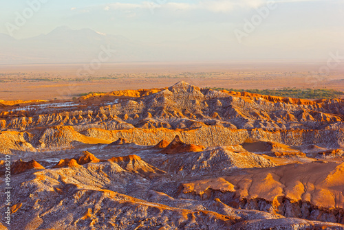Sunset over Atacama Desert panorama in San Pedro, Chile. Rock formation patterns left by volcanic activity of the past in the desert vastness.
