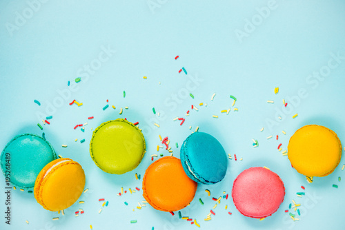 Door stickers Macarons Top view of colorful macaroons and sugar sprinkles arranged over blue background.