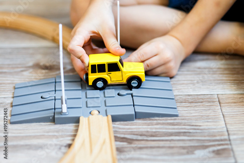 a boy playing with a wooden toy set with cars, modern train