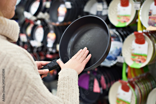 Woman chooses frying pan in crockery store