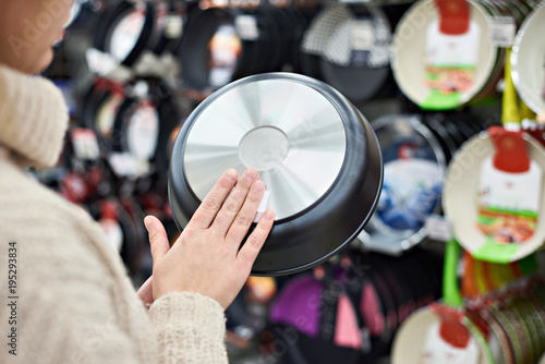 Woman chooses frying pan in crockery store