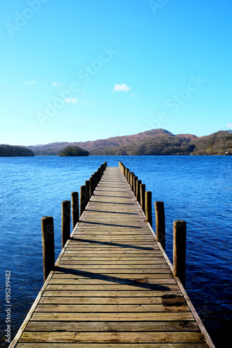 very long beautiful wooden jetty, jutting out from the centre of the image into a calm blue lake with hills of forest and meadows in background