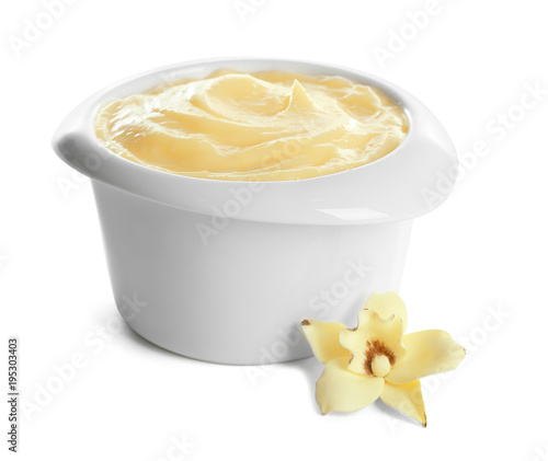 Photo Tasty vanilla pudding in ramekin and flower on white background