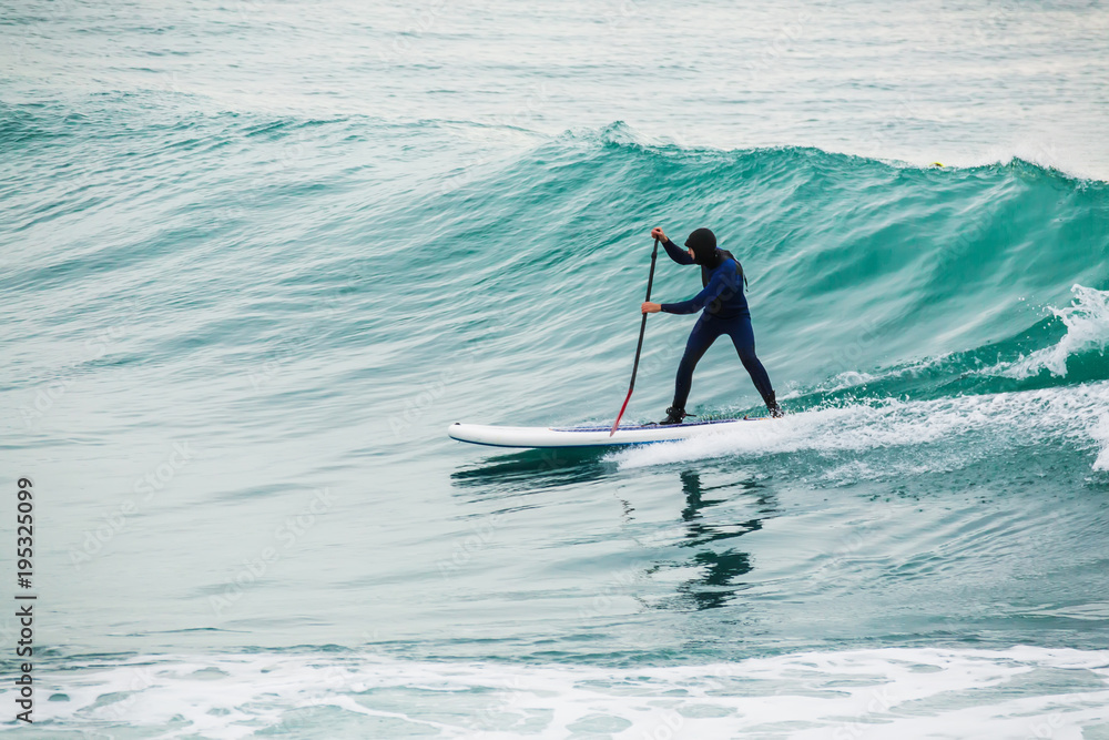 surfer on stand up paddle board on blue wave foto poster wandbilder bei europosters