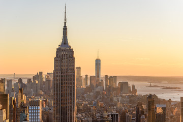 New York City - USA. View to Lower Manhattan downtown skyline with famous Empire State Building and One World Center and skyscrapers at sunset.