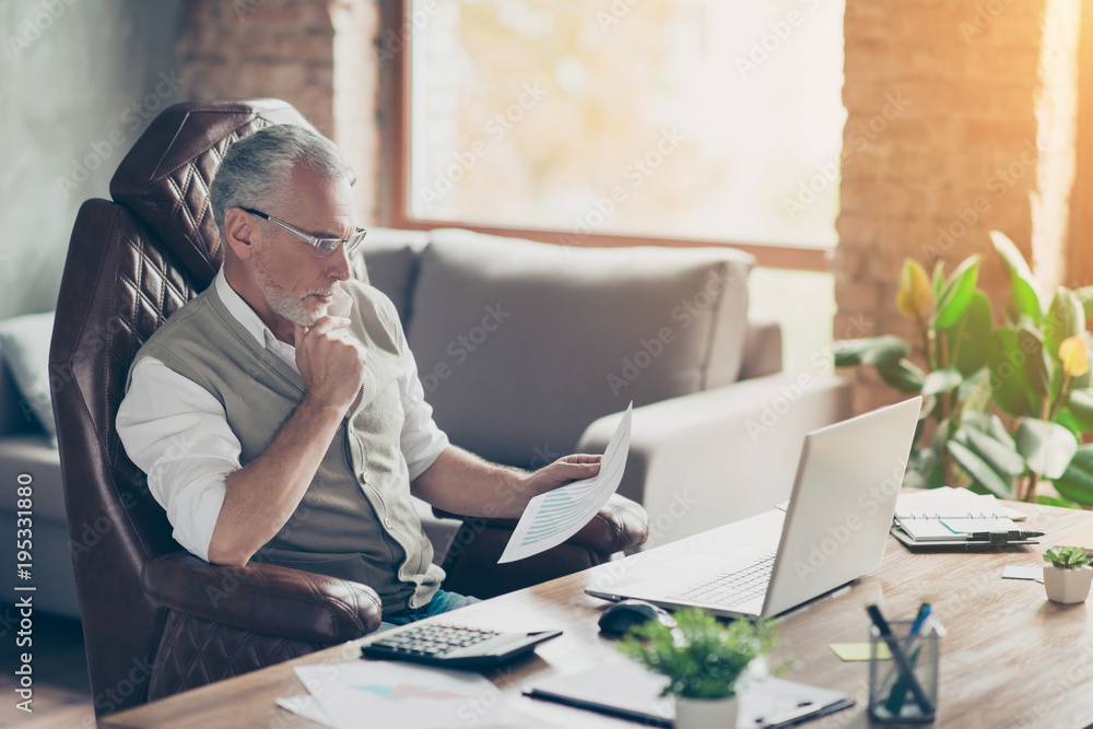 Fototapety, obrazy: Plan profit paper cost debt credit bill success tax people armchair chair freelance company owner concept. Side profile view photo of serious pensive analyzing minded economist holding graphs in hand