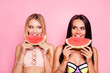 canvas print picture Portrait of hot, comic, childish, cute, seductive, blonde, brunette tourists, ladies in swim suits looking to each other with eye, having lobes of watermelon in hands, isolated on pink background