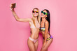 Leinwanddruck Bild Attractive, blonde, brunette, seductive, pretty, charming, joyful, fit, stylish, cheerful, trendy tourists, ladies in swim suits shooting self portrait on smart phone, posing over pink background