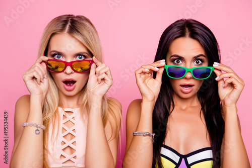 WTF! Pretty, charming, astonished, frustrated impressed, stressed, depressed ladies, tourists looking out glasses with wide open eyes and mouth, holding eyelets with hands, isolated on pink background