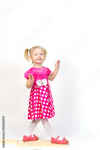 bb9f14df03 Little girl 3 years old in a red dress with bows in her hair. Beautiful girl  in a beautiful fluffy dress posing against a white wall.