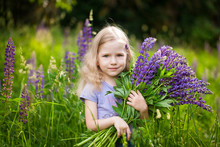 Cute Girl With A Bouquet Of Purple Lupine Flowers