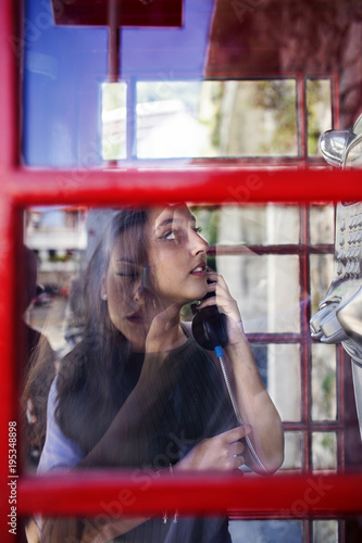 Fotografie, Obraz  Teenage girl calling by phone from a red telephone booth