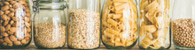 Various Uncooked Cereals, Grains, Beans And Pasta For Healthy Cooking In Glass Jars On Wooden Table, White Background, Close-up, Wide Composition. Clean Eating, Vegan, Balanced Dieting Food Concept