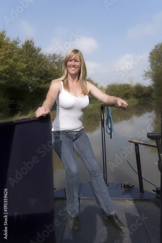 Woman using the tiller to steer a narrowboat along a canal in the UK Fototapete